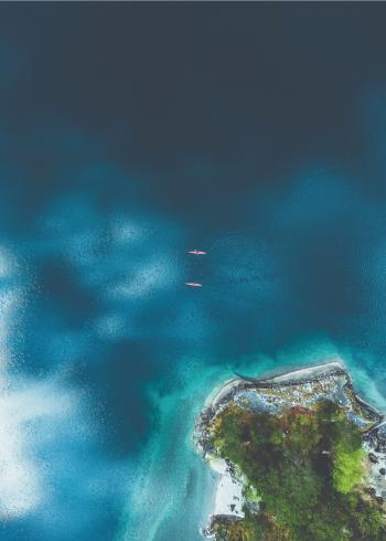 fotoplakat af to der sejler i kano i det blå ocean i tropiske omgivelser