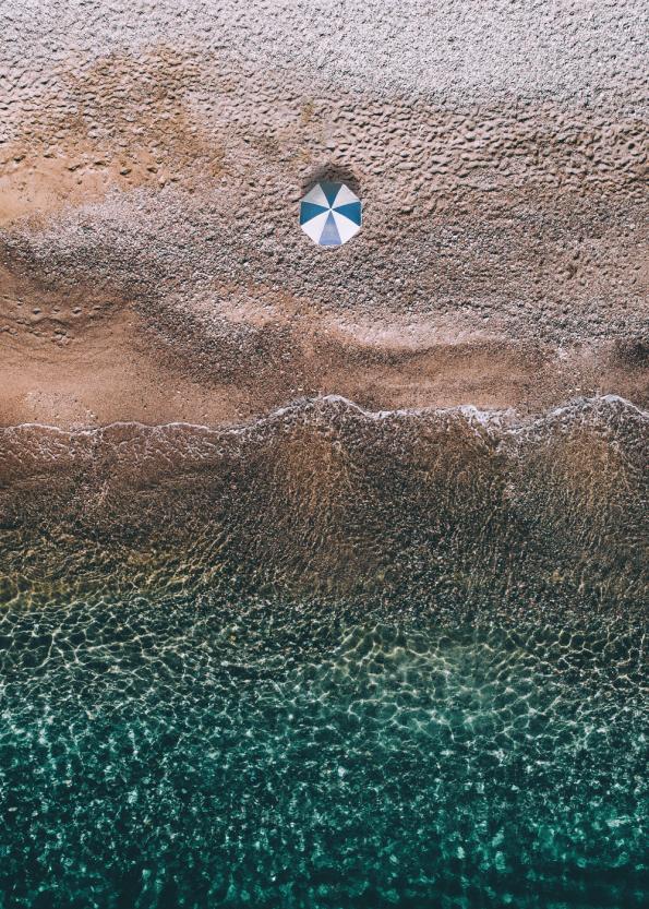 tropisk stand med flot klart blåt vand med parasol