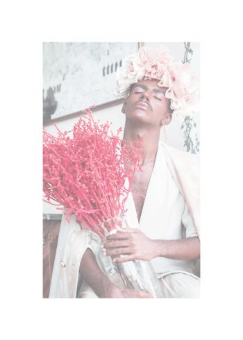 Indisk mand klædt i hvidt og makeup der holder en vase med lyserøde blomster.