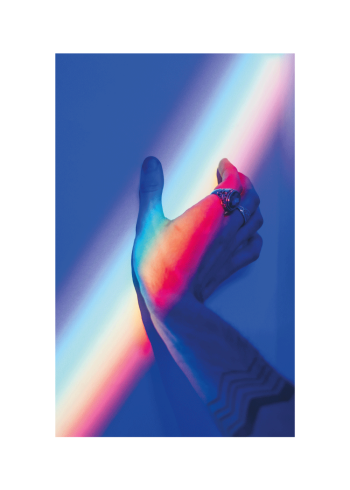En hånd i et mørkt rum der oplyses af lysende pride flag