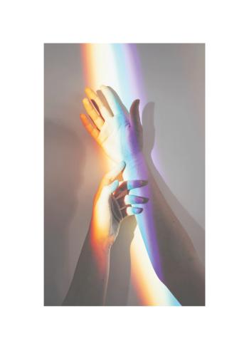 To hænder dækket af regnbuefarvet lys