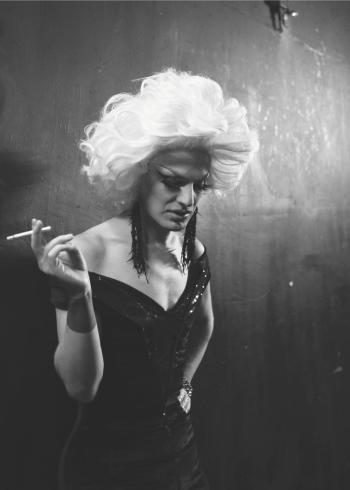 Transperson i sort kjole og med paryk der ryger en cigaret